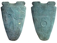 13. Palette of King Narmer Location: Nekhen, Egypt Artist: N/A Date: c. 3,000-2,920 B.C.E Culture: Predynastic Egypt Period: Ancient Egypt Medium/Material: Greywacke Theme(s): weaponry, leadeship,  Form: Form and shape used to create the structure of the actual palette as well as the designs on both the front and back. Hierarchy of scale seen. Function: A votive or gift offering by the King to his