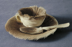 138. Object (Le Dejeuner en fourrure) Location: ? Artist: Meret Oppenheim Date: 1936 C.E. Culture: ... Period/Style: Later Europe/America Medium/Material: Fur, cup, saucer, spoon Theme(s): femininity Form: ... Function: ... Content: cup, saucer, and spoon covered in fur Context:The work, which originated in a conversation in a Paris cafe, is the most frequently-cited example of sculpture in the surrealist movement. It is also noteworthy as a work with challenging themes of femininity. Cross Cultural Connection(s):