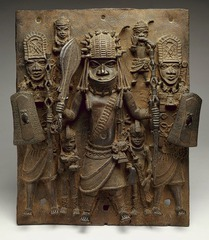 169. Wall plaque, from Oba's Palace Location: Benin Kingdom (near Nigeria) Artist: Edo peoples Date: 16th century C.E. Culture: Benin Period/Style: 16th Century Benin Medium/Material: Cast brass Theme(s): Royalty, ceremony, authority Form: hierarchy of scale to show importance of figures in the plaque. medium-deep relief.  Function: to depict an Oba and his attendants  Content: central figure is an Oba because of his distinctive coral beaded regalia. Attendants hold shields above his head either to protect him from attack or possibly from the sun; a privilege only afforded to an Oba.  Context: The plaque originally hung alongside many others on posts throughout the palace of the Oba. The order of their placement on these posts would have told the history of the royal lineage of Benin's Obas, who traced their dynasty all the way back to Oranmiyan, whose son was the first Oba of Benin.