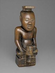 171. Ndop (portrait figure) of King Mishe miShyaang maMbul Location: Democratic Republic of the Congo Artist: ? Date: c. 1760-1780 C.E. Culture: Kuba peoples Period/Style: Medium/Material: Wood Theme(s): authoritative position, spiritual presence  Form: position shows a relaxed being in a higher position than others. Idealistic depiction of King's spiritual being.  Function: took the place of the king in his absence Content: male figure with a large head (represent knowledge), headwear, holding probably a cup, symbol marking on the base Context: created after king's passing. earliest African wood sculpture and ndop in existence. Kept in king's shrine along with other