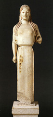 28. Peplos Kore from the Acropolis. Archaic Greek. c. 530 B.C.E. Marble, painted details. -Athens, Greece -woman (possibly Athena because of adorned dress, headdress, and bow) -function: honoring Athena (either an offering or a depiction) -raised left arm and archaic smile (shows well-being, not emotion) representative of archaic style -brightly painted with animal figures on clothing to represent fertility and prosperity -kore (young women) statues were offerings to goddesses -closely tied to Greek gods/religion