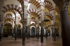 56. Great Mosque Location: Córdoba, Spain Date: c. 785-786 C.E., eighth-tenth centuries Period/Style: Umayyad Caliphate (Islamic Art) Medium/Material: Stone masonry Theme(s): worship Form: Double-arched columns, articulated in alternating bands of color; voussoirs Function: worship Content: columns are spoil, hypostyle mosque, kufic calligraphy, complex dome over mihrab (squinches)  Context: ... Cross Cultural Connection(s):