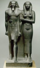 King Menkaura and queen. Ancient Mediterranean. Old Kingdom, fourth dynasty. 2490-2472 BCE. Medium:slate Form: realistic, 8ft, slate Function: to display Menkaura as royalty Content: shows king menkaura (smaller pyramid) and a woman(wife, other wife, mother, Hathor) Context: after or during his reign
