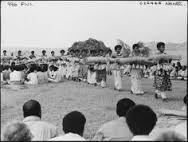 Processional welcoming Queen Elizabeth II to Tonga with Ngatu launima (tapa cloth). Tonga, central Polynesia. 1953 C.E. Multimedia performance (costume; cosmetics, including scent; chant; movement; and pandanus fiber/hibiscus fiber mats), photographic documentation.